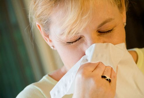woman using tissue to blow nose