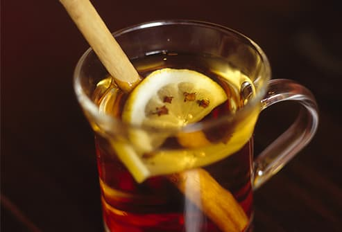 Hot toddy with lemon, cloves and cinnamon stick