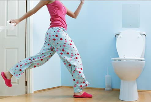 woman running to bathroom
