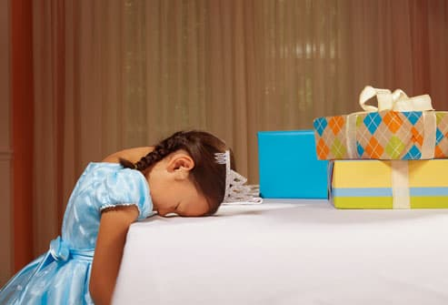 Small girl asleep at her own birthday party