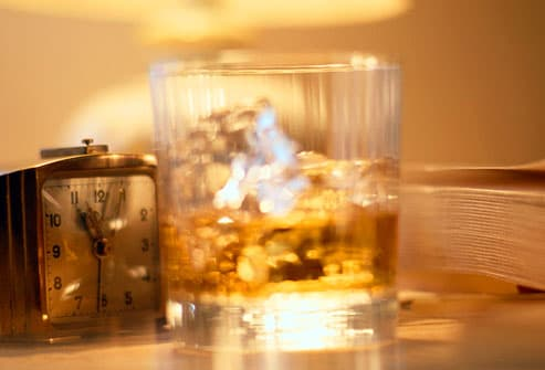 Glass of whiskey and alarm clock on bedside table