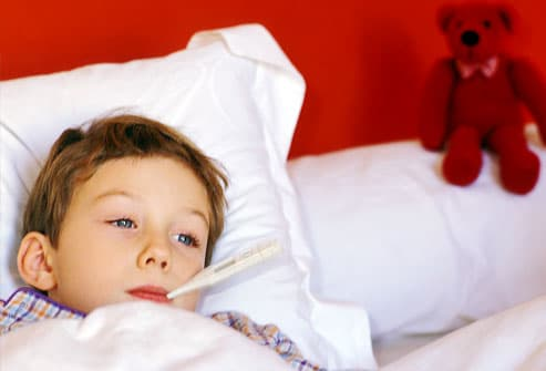 Boy in bed with fever in red bedroom