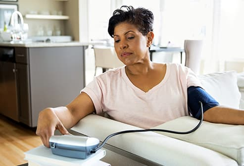 mature woman checking blood pressure at home