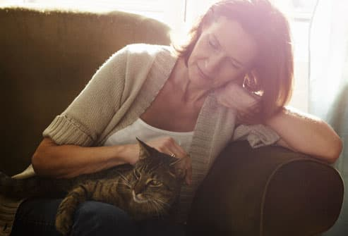 mature woman stroking cat
