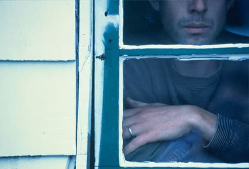 Man sitting, looking out of house window
