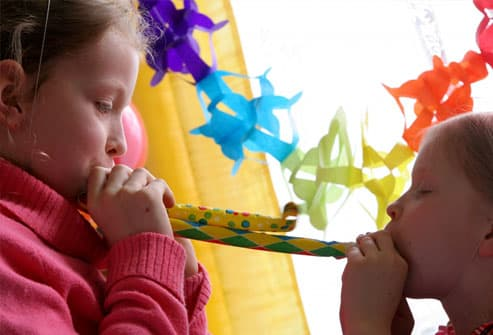 Two girls blowing noisemakers at party