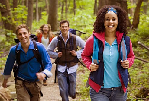 Group of adequately covered hikers in forest