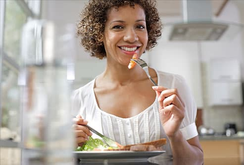 Woman eating at kitchen table