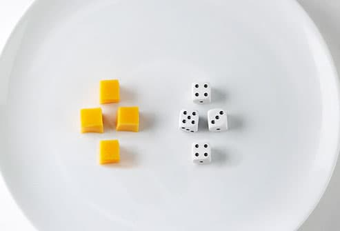 Cubes of cheese and dice on plate