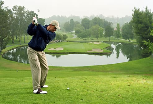 Golfer about to tee off on cool morning