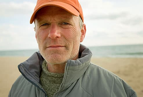 man wearing baseball cap on beach