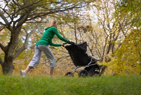 woman pushing stroller on path