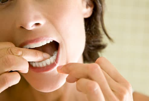 Close-up of a woman flossing her teeth