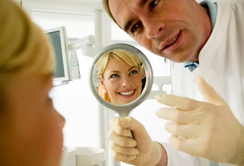 Dentist showing a woman her smile in a mirror