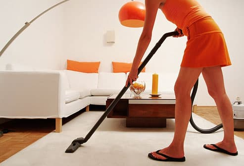 Woman vacuuming living room rug