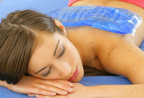 Woman lying with ice pack on back