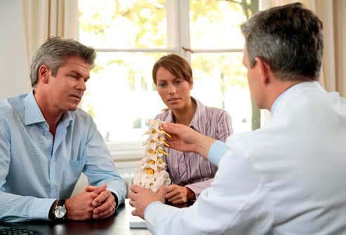Couple discussing spine with doctor
