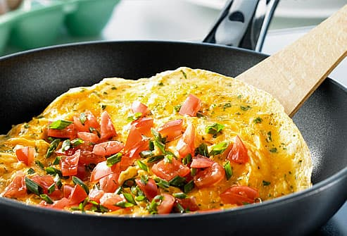 Omelette with pieces of tomato in frying pan
