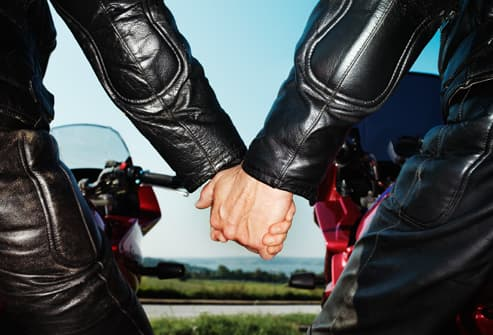 Couple holding hands on motorcycles