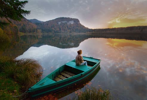 Mature woman watching the sunset from a rowboat