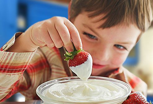 Boy dipping strawberry into plain yogurt