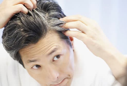 man looking at gray hair in mirror