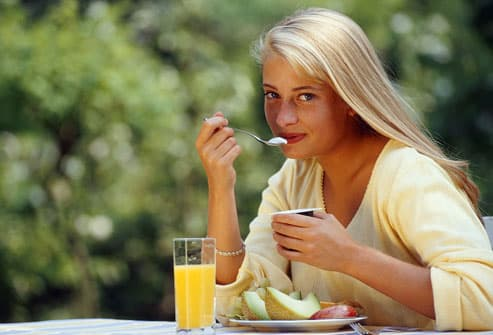 Young woman eating breakfast outdoors