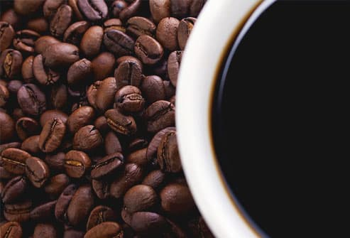 Close-up of coffee beans and cup, cup out of focus