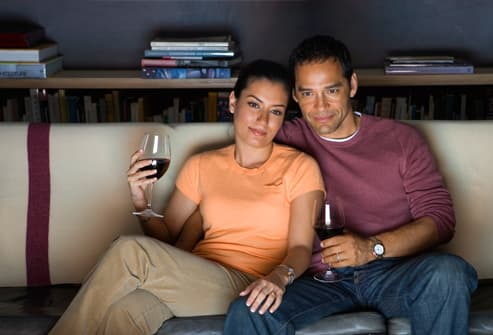 Couple watching television and drinking red wine