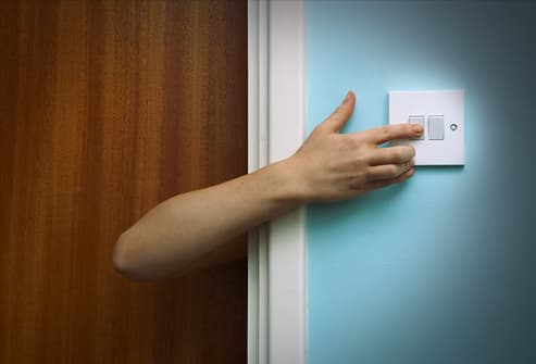 Person reaching round door to touch light switch