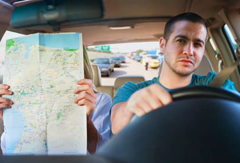 Man driving while his wife navigates with a map