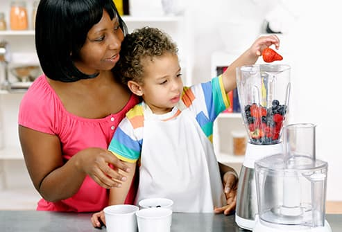 mother and daughter making smoothies