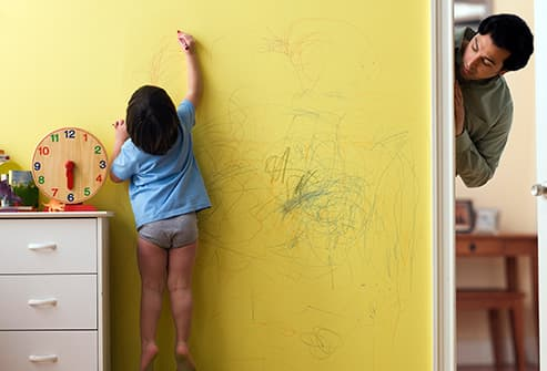 boy coloring on wall