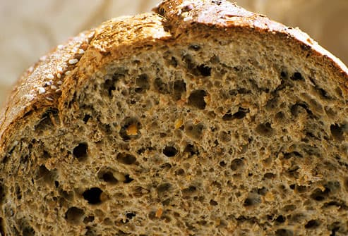 Cut rustic loaf of whole wheat bread