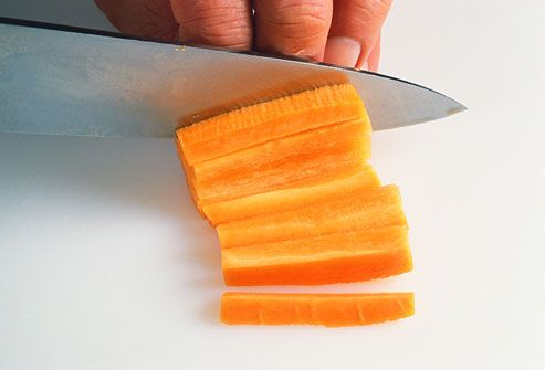 Person cutting a carrot