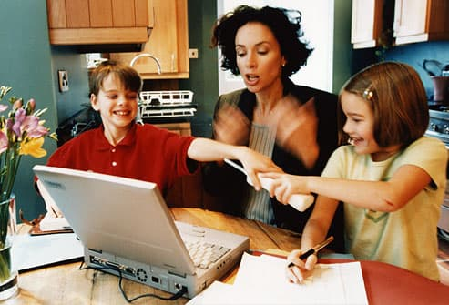 Stressed mom with children playing around laptop
