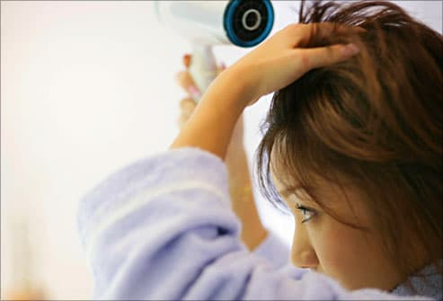 woman using blow dryer