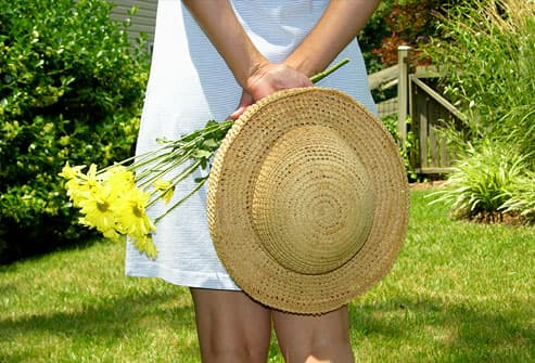 Young woman with straw hat and flowers