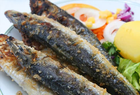 Sardines on plate with vegetables