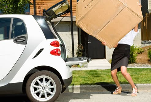 Woman Loading Giant Box Into Car