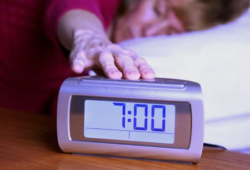 Woman turning away alarm clock