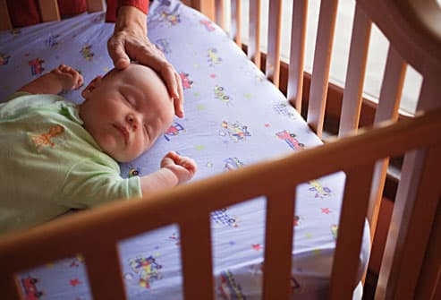 Mother Soothing Baby In Crib