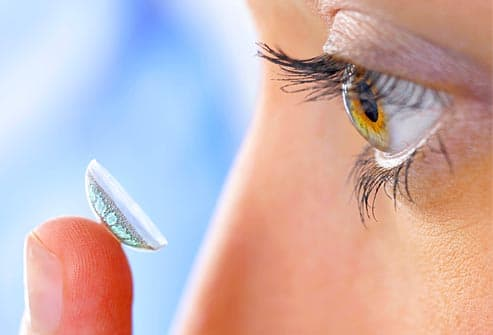 woman applying contact lense