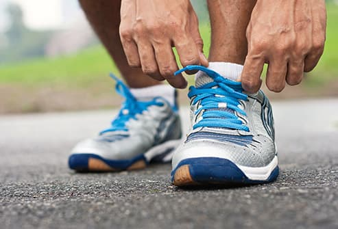 man tying running shoes close up