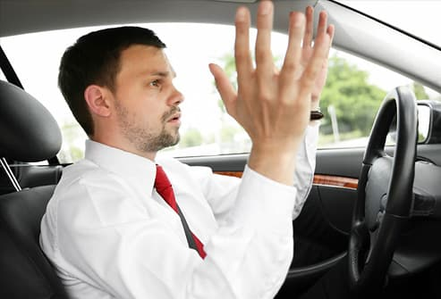 Driver raising hands in frustration in traffic