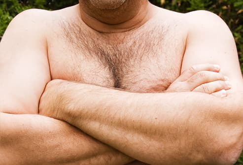 Man crossing arms over his bare chest
