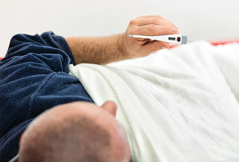 man in bed reading digital thermometer