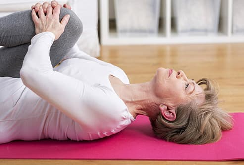 mature woman on floor stretching