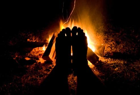 feet warmed by campfire