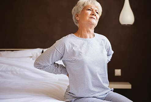 senior woman with back pain on bed